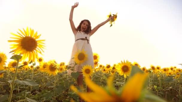 Roztomilé dítě dívka v žlutých zahrada slunečnice slunečního záření v létě. životní styl krásný západ slunce holčička v slunečnice. zpomalené video. Dívka teenager a slunečnice pole koncepce zemědělství