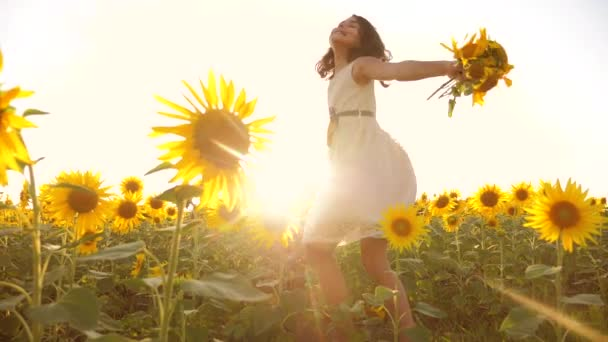 Aranyos életmód gyermek lány sárga kert napraforgó napfényt nyáron. gyönyörű naplemente kislány napraforgóban. Slow motion videót. tinédzser lány és napraforgó mező mezőgazdasági koncepció