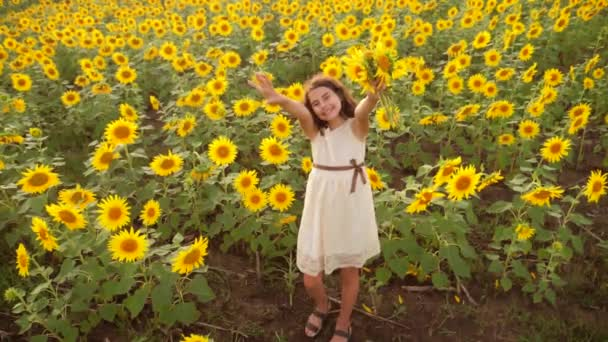 Happy little girl on the field of sunflowers in summer. beautiful little girl in sunflowers. slow lifestyle motion video. girl teenager and sunflowers field concept agriculture