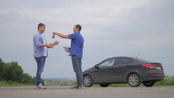 two men make deal. man handshake hands over the keys seller driver makes car the auto insurance slow motion video sale sells used cars. Buying rent a car . man car insurance sale of used cars concept
