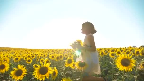 Happy little girl running happy free across field with sunflowers. slow motion video. smelling big sunflower on lifestyle summer field. Delight of a pleasant smell. Summer holiday. concept happiness