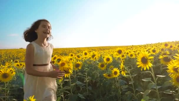 Happy little girl lifestyle running happy free across the field with sunflowers. slow motion video . smelling big sunflower on summer field. Delight of a pleasant smell. Summer holiday. concept
