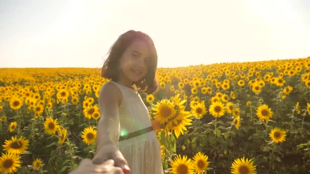 Dad and daughter walking along the field with sunflowers at sunset holding hands First-person view. Slow motion video. lifestyle follow me. little girl and boy teenager run by the hand over the field
