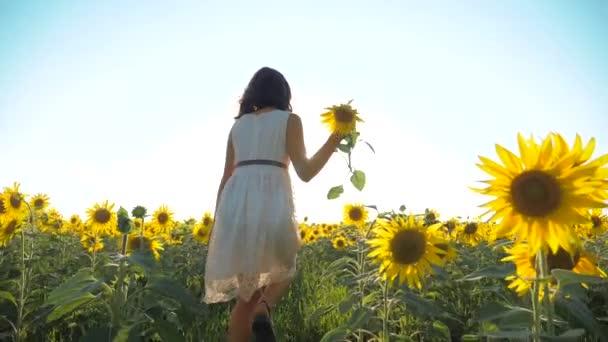 Malé radostné holčičky běží šťastný zdarma přes pole s slunečnice. zpomalené video. vonící velké slunečnice na letní pole. Radost z příjemné vůně. Letní dovolená. pojem štěstí dětství