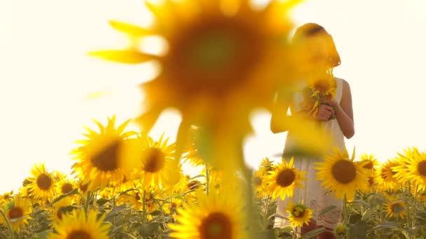 Šťastná malá holka teen vonící slunečnice na hřišti v létě. zpomalené video. dospívající dívka stojící v poli s slunečnice drží květiny životní styl při západu slunce. dívka dětství