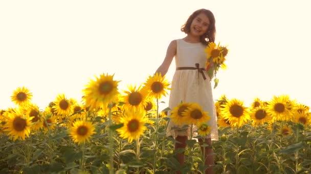 Šťastný malý teen holka vonící slunečnice kýchne alergická na květiny na hřišti v létě. zpomalené video. dívka dětství slunečnice zemědělství koncepce kýchne alergická na květiny. Děvče