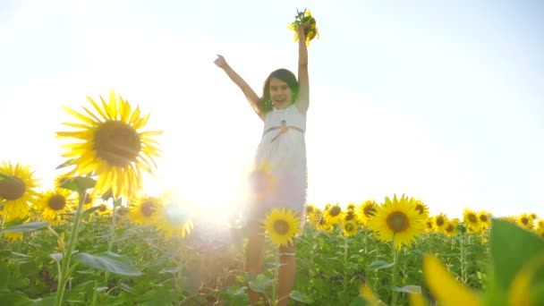 Happy little girl on lifestyle the field of sunflowers sunlight in summer. beautiful sunset little girl in sunflowers. slow motion video. girl teenager and sunflowers field concept agriculture