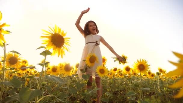 Roztomilé dítě dívka v žlutých zahrada slunečnice slunečního záření v létě. krásné životní styl slunce holčička v slunečnice. zpomalené video. Dívka teenager a slunečnice pole koncepce zemědělství