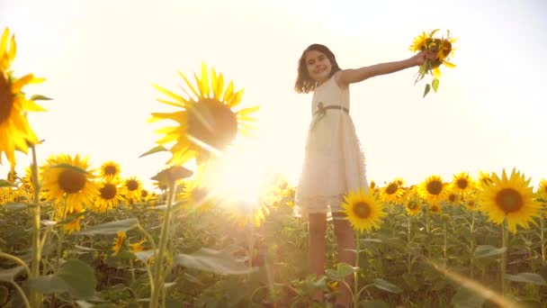 Cute child lifestyle girl in yellow garden of sunflowers sunlight in summer. beautiful sunset little girl in sunflowers. slow motion video. girl teenager and sunflowers field concept agriculture