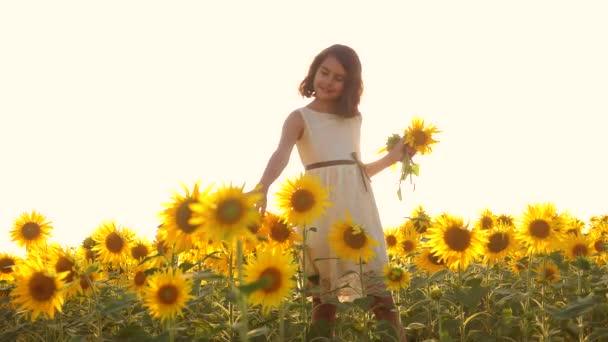 Šťastná holčička na pole slunečnic slunečního záření v létě. krásný západ slunce malá holčička v slunečnice. zpomalené video. Dívka teenager a slunečnice životní styl pole koncepce zemědělství