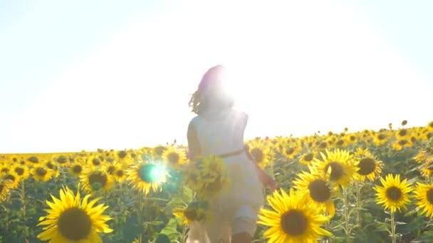 Happy little girl running happy free across the field with sunflowers. slow motion video. smelling big sunflower on summer field. Delight of a pleasant smell lifestyle. Summer holiday. concept