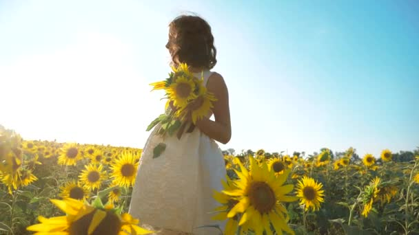 Happy little girl running happy free across the field with sunflowers lifestyle. slow motion video . smelling big sunflower on summer field. Delight of a pleasant smell. Summer holiday. concept