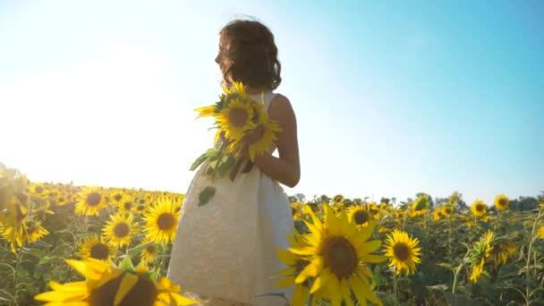 Malé radostné holčičky běží šťastný zdarma přes pole s slunečnice životní styl. zpomalené video. vonící velké slunečnice na letní pole. Radost z příjemné vůně. Letní dovolená. koncepce