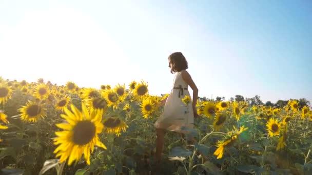 Malé radostné holčičky běží šťastný zdarma přes pole s slunečnice. zpomalené video. vonící velké slunečnice na letní pole. Radost z příjemné vůně. Letní dovolená. pojem životní styl