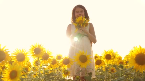 Boldog kis lány tini szagú a területen napraforgó, nyáron. Slow motion videót. lány tinédzser állva egy területen napraforgó gazdaság virágok, a napfény naplemente. lány gyermekkori életmód