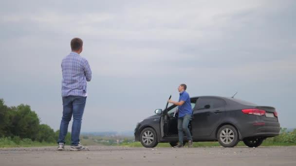 muž test drive car.two muži vypořádat. Člověče prodávající řidič dělá auto auto pojištění zpomalené video prodej prodává ojetá auta. Nutnosti půjčit auto. muž auto pojištění životní styl prodej ojetin koncepce