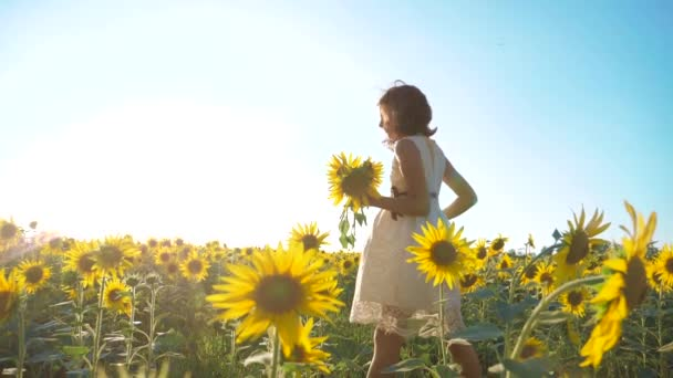 Happy little girl running happy free across the field with sunflowers. slow motion video. smelling big sunflower on summer field. Delight lifestyle of a pleasant smell. Summer holiday. concept