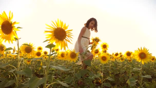 Cute child girl in yellow lifestyle garden of sunflowers sunlight in summer. beautiful sunset little girl in sunflowers. slow motion video. girl teenager and sunflowers field concept agriculture