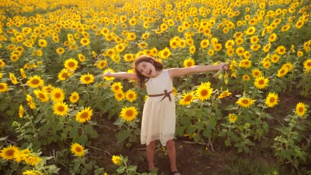Happy little girl on the field of sunflowers in summer. beautiful little girl in sunflowers. slow motion video. girl teenager and lifestyle sunflowers field concept agriculture