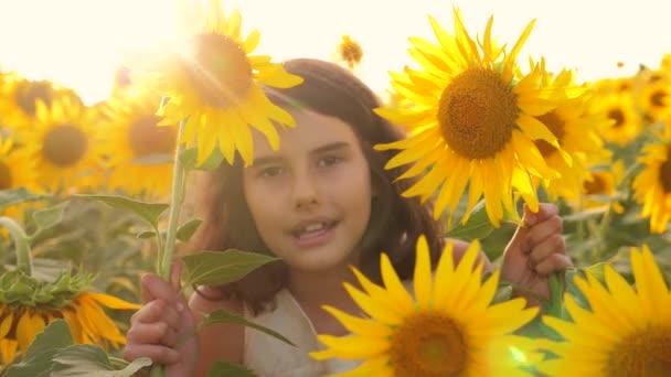 Happy portrét holčička na pole slunečnic v létě. krásný portrét holčička v slunečnice. zpomalené video. Dívka teenager a životního stylu slunečnice pole koncepce zemědělství