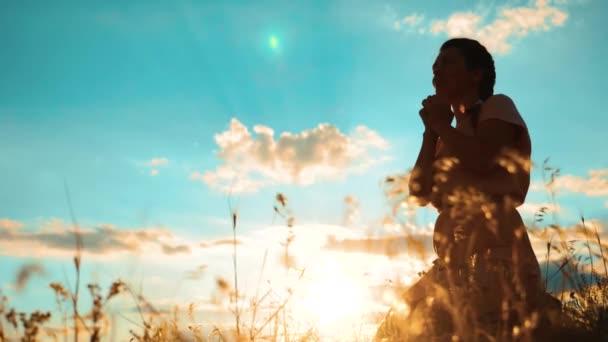 Dívka složila si ruce v modlitbě silueta při západu slunce. Žena se modlí na kolenou. zpomalené video. Dívka složila si ruce v modlitbě modlit se k Bohu. dívka se modlí požádá o odpuštění za hříchy pokání