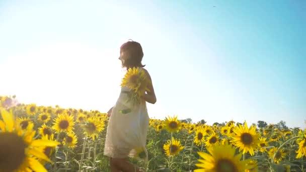 Malé radostné holčičky běží šťastný zdarma přes pole s slunečnice. zpomalené video. vonící velké slunečnice na letní pole. životní styl potěšení příjemnou vůni. Letní dovolená. koncepce