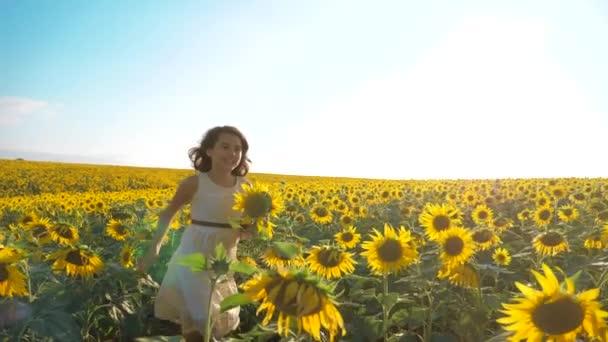 Malé radostné holčičky běží šťastný zdarma přes pole s slunečnice. zpomalené video. vonící velké slunečnice na letní pole. Radost z příjemné vůně. Letní dovolená. pojem štěstí dívka