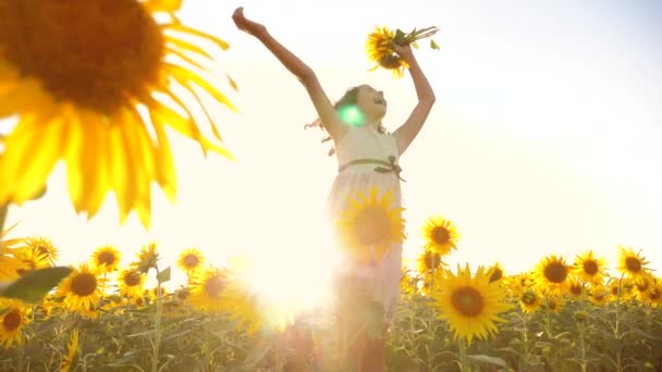 Cute child girl in yellow garden of sunflowers sunlight in summer. beautiful sunset little girl in sunflowers lifestyle. slow motion video. girl teenager and sunflowers field concept agriculture