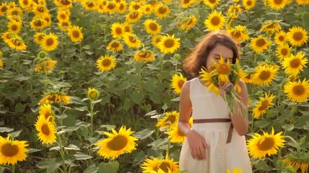 Boldog kislány nyári napraforgó életmód területén. szép kislány napraforgóban. Slow motion videót. tinédzser lány és napraforgó mező mezőgazdasági koncepció