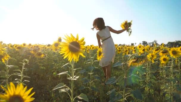Boldog lány boldog szabadon szalad a mezőn, a napraforgó. Slow motion videót. illatos nagy napraforgó nyári mező. Örömére egy kellemes illata. Nyári szünet. koncepció boldogság lány