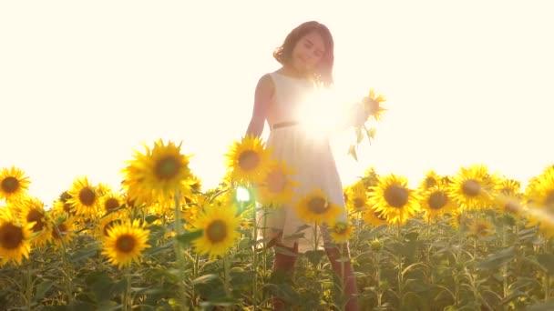 Boldog kis lány a területen napraforgó napfényt nyáron. gyönyörű naplemente kislány napraforgóban. Slow motion videót. tinédzser lány és napraforgó mező életmód fogalmát mezőgazdasági