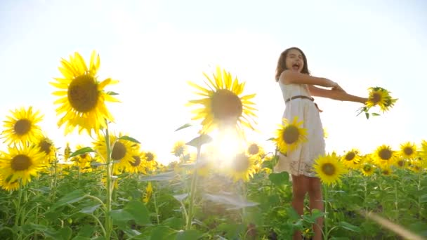 Happy little lifestyle girl on the field of sunflowers sunlight in summer. beautiful sunset little girl in sunflowers. slow motion video. girl teenager and sunflowers field concept agriculture