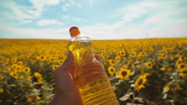 gazda, kezében egy műanyag üveg napraforgó olaj az ő életmód kézi field-napfényben. Slow motion videót. a kék ég háttér mezőgazdasági koncepció napraforgóolaj üveg gazdálkodás naplemente mező. Férfi farmer