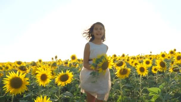Boldog lány boldog szabadon szalad a mezőn, a napraforgó. Slow motion videót. illatos nagy napraforgó nyári mező. Örömére egy kellemes illata. életmód nyaralás. koncepció