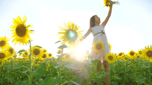 Boldog kis lány életmód a területen napraforgó napfényt nyáron. gyönyörű naplemente kislány napraforgóban. Slow motion videót. tinédzser lány és napraforgó mező mezőgazdasági koncepció