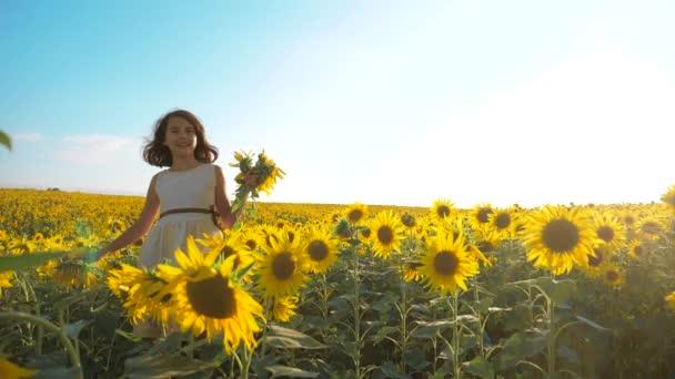 Malé radostné holčičky běží životní styl šťastný zdarma přes pole s slunečnice. zpomalené video. vonící velké slunečnice na letní pole. Radost z příjemné vůně. Letní dovolená. koncepce