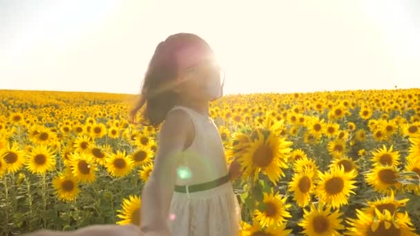 Dad and daughter walking along the field with sunflowers at sunset holding hands First-person view. Slow motion video. follow me. little girl and boy teenager run by the hand over the field with