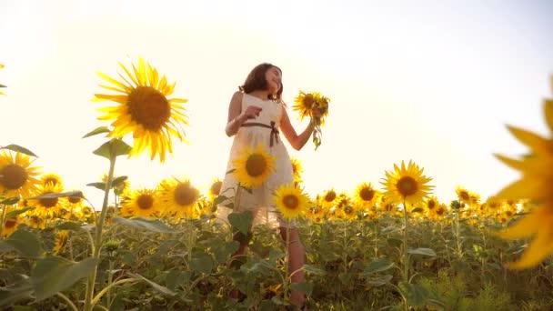 Roztomilé dítě dívka v žlutých zahrada slunečnice slunečního záření v létě. krásný západ slunce životní styl holčička v slunečnice. zpomalené video. Dívka teenager a slunečnice pole koncepce zemědělství