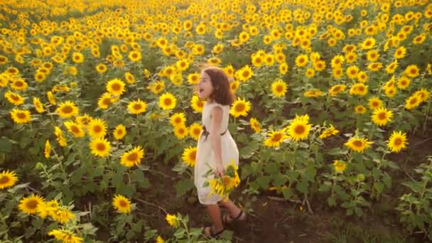 Happy little girl on the field of sunflowers in summer. beautiful little girl in sunflowers. slow motion video. girl lifestyle teenager and sunflowers field concept agriculture
