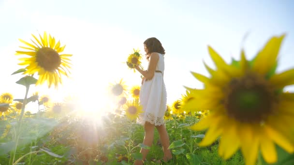 Happy little girl on the field of sunflowers sunlight lifestyle in summer. beautiful sunset little girl in sunflowers. slow motion video. girl teenager and sunflowers field concept agriculture