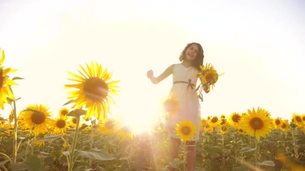 Roztomilé dítě dívka v žlutých zahrada slunečnice životního stylu slunečního záření v létě. krásný západ slunce malá holčička v slunečnice. zpomalené video. Dívka teenager a slunečnice pole koncepce zemědělství