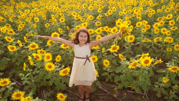 Happy little girl on the field of sunflowers in summer. beautiful little girl in sunflowers. slow motion video. lifestyle girl teenager and sunflowers field concept agriculture