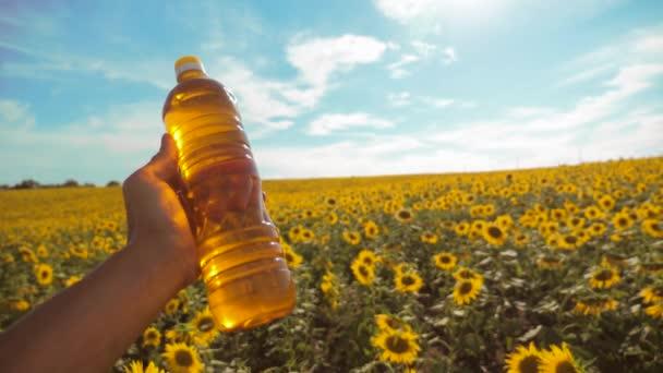 Férfi farmer feltárása terén a napraforgó. gazda, kezében egy műanyag üveg napraforgóolaj a kezében mező napfény. életmód slow motion videót. kék ég háttér mezőgazdasági koncepció