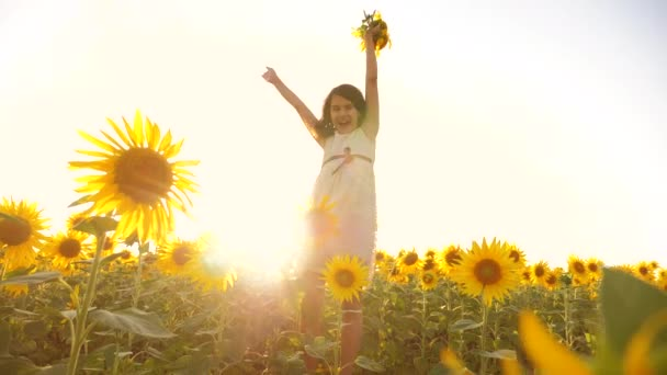 Cute child girl in yellow garden of sunflowers sunlight in summer lifestyle. beautiful sunset little girl in sunflowers. slow motion video. girl teenager and sunflowers field concept agriculture