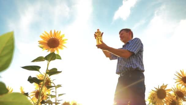 öreg ember gazda tartja a kezében egy műanyag palack napraforgó olaj áll a mező. Slow motion videót. életmód napraforgóolaj-termelési és kutatás mezőgazdasági gazdálkodás. nagy napraforgók ellen a