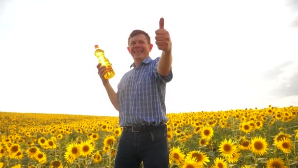 old man sunlight farmer sunflower oil concept agriculture. old man farmer holding in hand a plastic bottle sunflower oil stands lifestyle in the field. slow motion video. sunflower oil production and