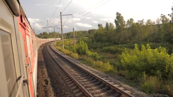 Railroad cars train ride on rails near the forest railway outside. slow motion video. The train with the carriages moves next to the forest. concept railroad lifestyle train cars and train journey
