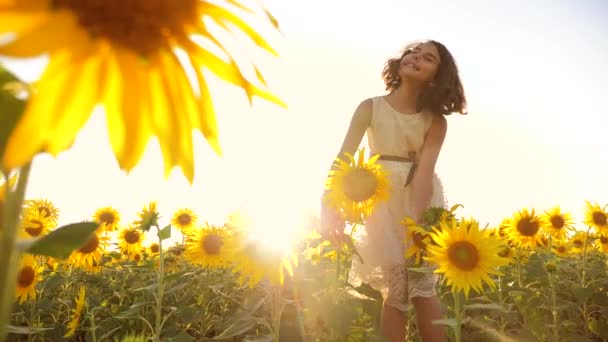 Happy little girl on the field of sunflowers sunlight in summer. beautiful sunset little girl in lifestyle sunflowers. slow motion video. girl teenager and sunflowers field concept agriculture