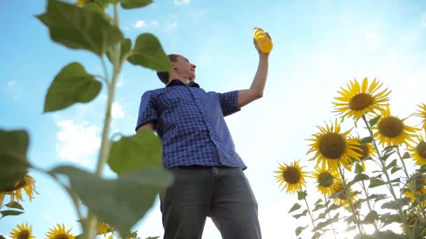 man farmer holding lifestyle in hand a plastic bottle sunflower oil stands in the field. slow motion video. sunflower oil production and research agriculture farming. large sunflowers against the blue