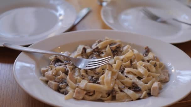 Italian spaghetti with sauce, mushrooms and basil leaf. slow motion video. Pasta tagliatelle with chicken meat and mushroom . Italian food concept cafe restaurant lifestyle